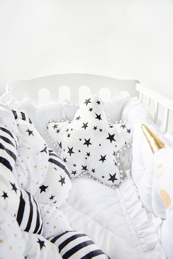 Уютная кроватка младенца с сформированным звездой одеялом одеяла валика и заплатки с звездами и черными нашивками стоковое изображение rf