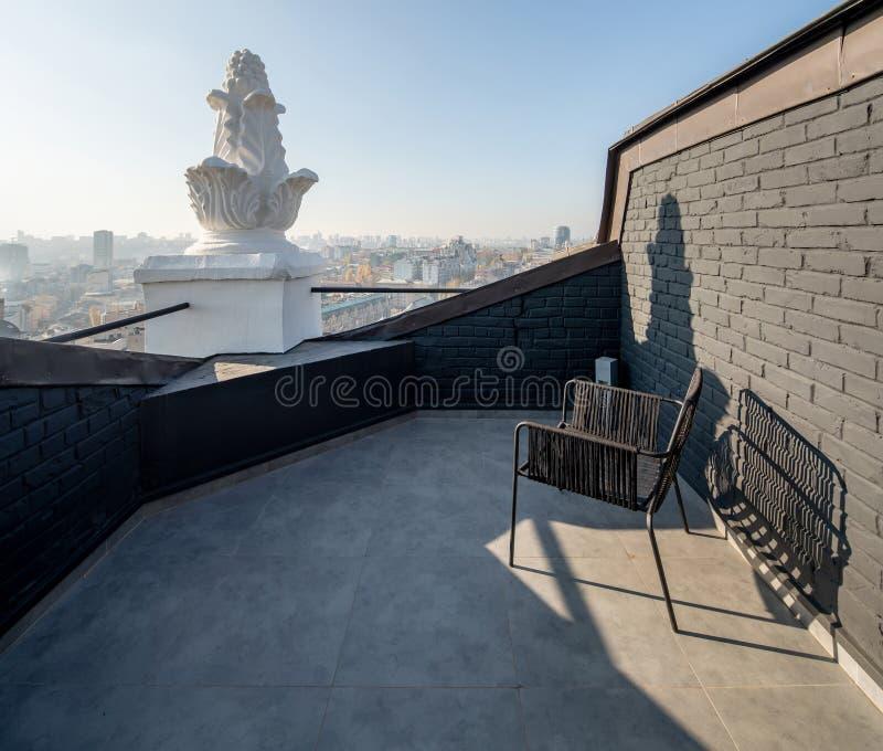 Уютная небольшая терраса с кирпичными стенами на солнечном backgroun городского пейзажа стоковое фото