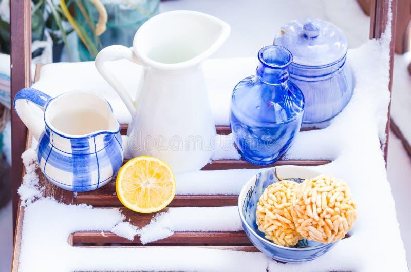 Уютная сцена с винтажными голубыми чашками, вазами, графинчиками в снеге стоковое фото
