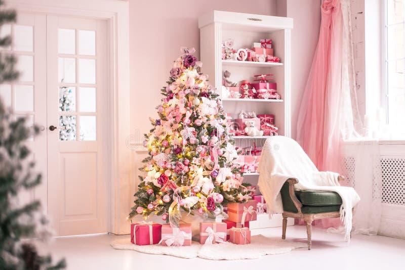 Уютная яркая комната детей с рождественской елкой, стулом и игрушками r стоковые фото