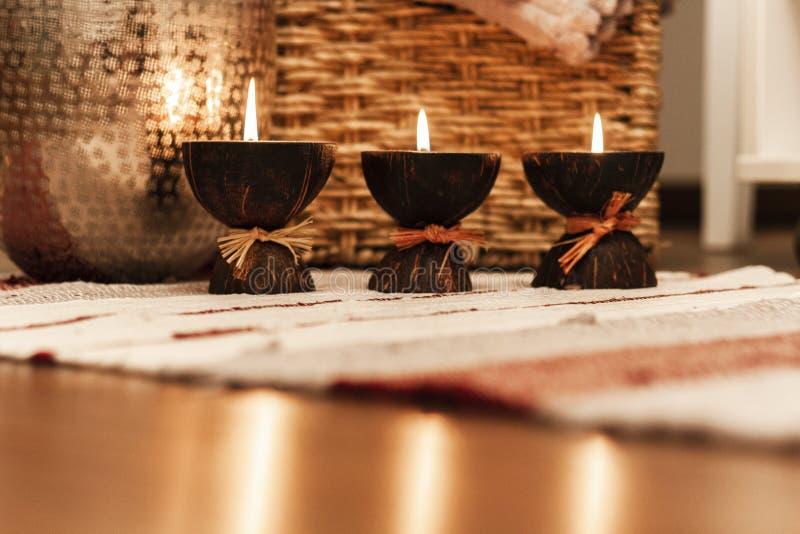 Уютное домашнее оформление интерьера, горящие свечи на пестротканом половике на предпосылке плетеной коробки соломы - изображении стоковое изображение