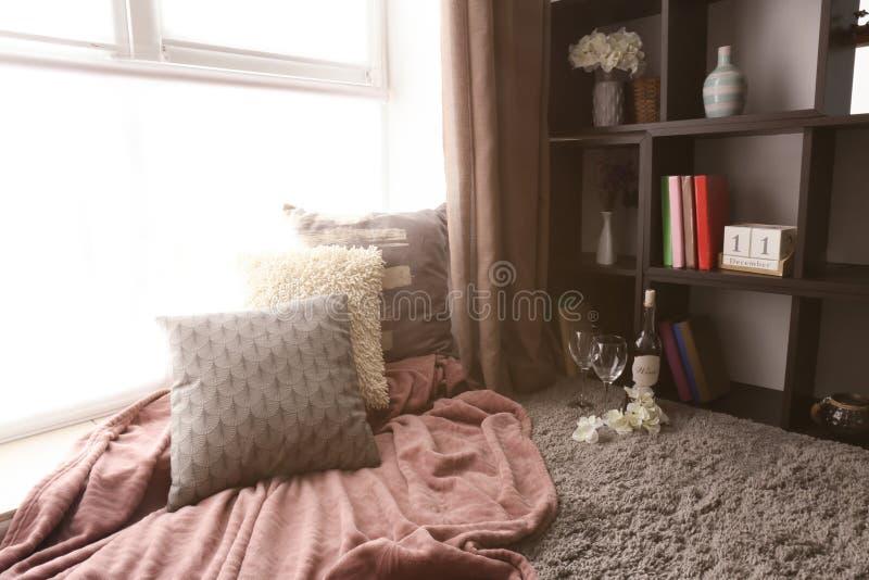 Уютное место для остатков с подушками и мягкой шотландкой около окна в комнате стоковое фото rf