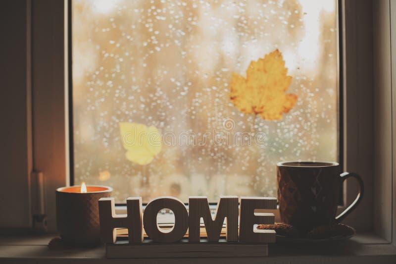 Уютное утро осени дома Горячие чай и свеча на окне в ненастном холодном дне стоковая фотография