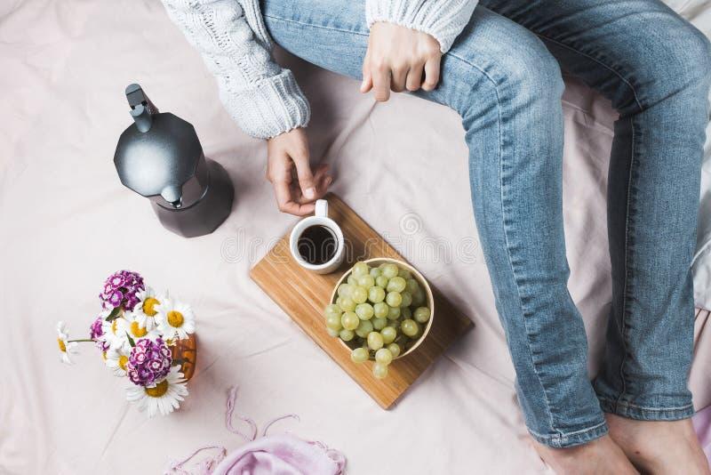 Уютное flatlay женщины в джинсах и мягком свитере сидя в ее кровати стоковое фото