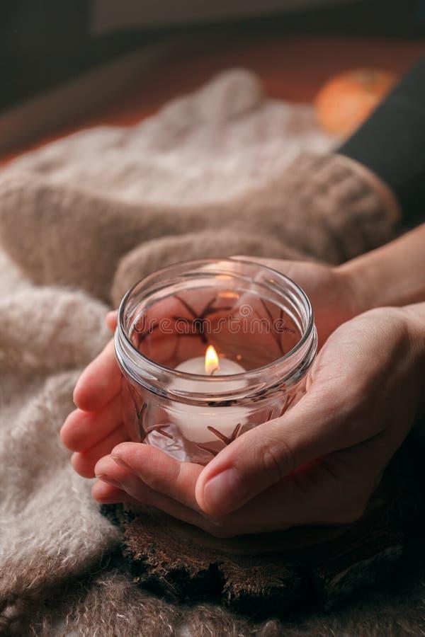 Уютные выходные зимы дома Руки держа свечку Концепция Hygge Детали натюрморта живущей комнаты стоковая фотография rf