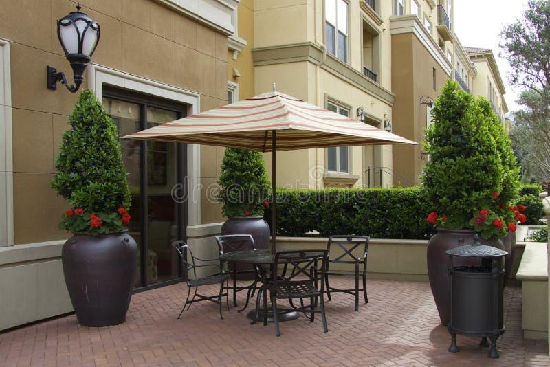 Уютные зонтик и таблица патио с стульями стоковая фотография