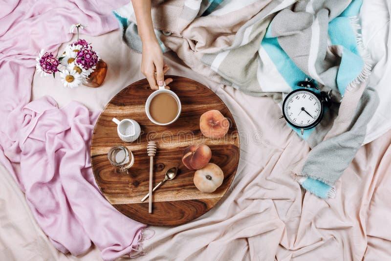 Уютные осень или зима flatlay деревянного подноса с чашкой кофе, персиками, сливочником с молоком завода, сиропом и ложками на па стоковое изображение rf