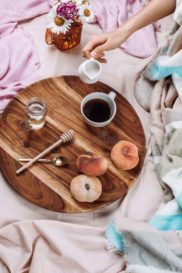 Уютные осень или зима flatlay деревянного подноса с чашкой кофе, персиками, сливочником с молоком завода стоковая фотография