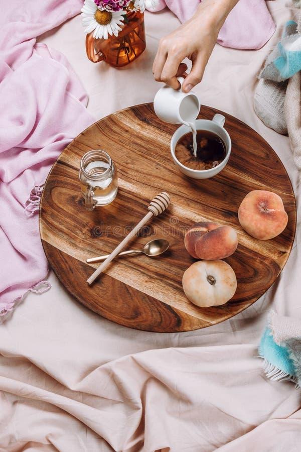 Уютные осень или зима flatlay деревянного подноса с чашкой кофе, персиками, сливочником с молоком завода стоковые фото