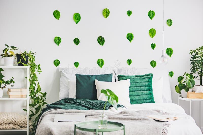 Уютные подушки на удобной большой королевской кровати в яркой спальне внутренней в элегантной квартире стоковая фотография