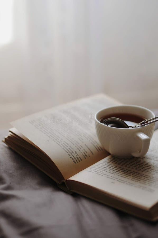 Уютный домашний натюрморт: чашка горячего чая с сеткой и раскрытой книгой на серой кровати Концепция уюта и чтения утро ослабляя стоковые фото
