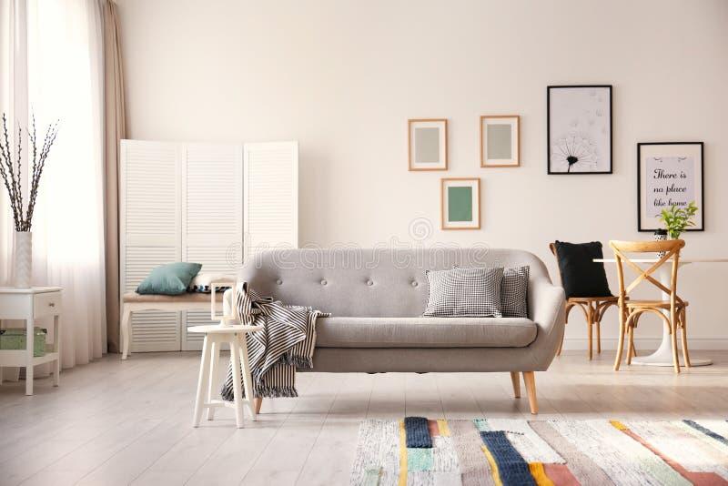 Уютный интерьер живущей комнаты с софой стоковая фотография