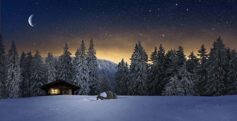 Уютный коттедж в зимнее время ночью стоковые изображения