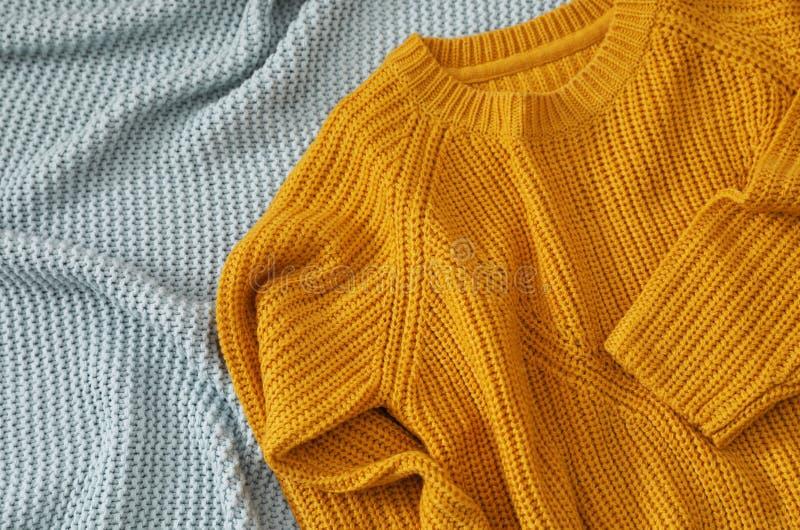 Уютный связанный свитер на одеяле, над взглядом стоковые фото