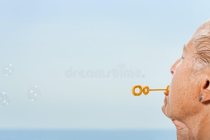 дуя женщина старшия пузырей стоковое фото