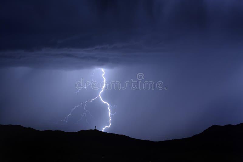 Удар молнии на горе с радиовышкой стоковое фото