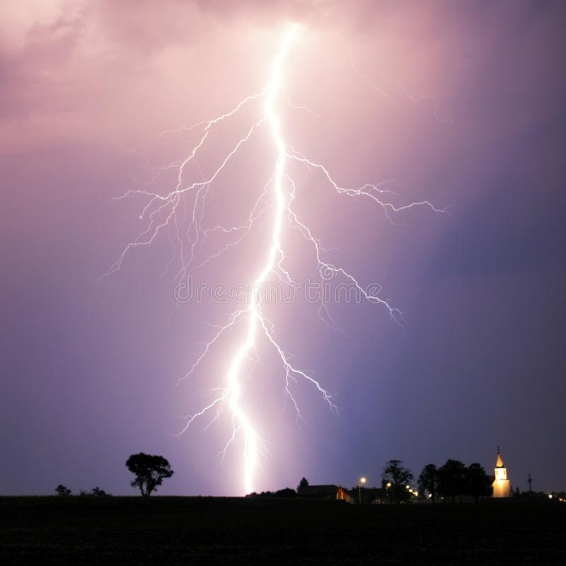 Удар молнии на strom над деревней стоковое изображение