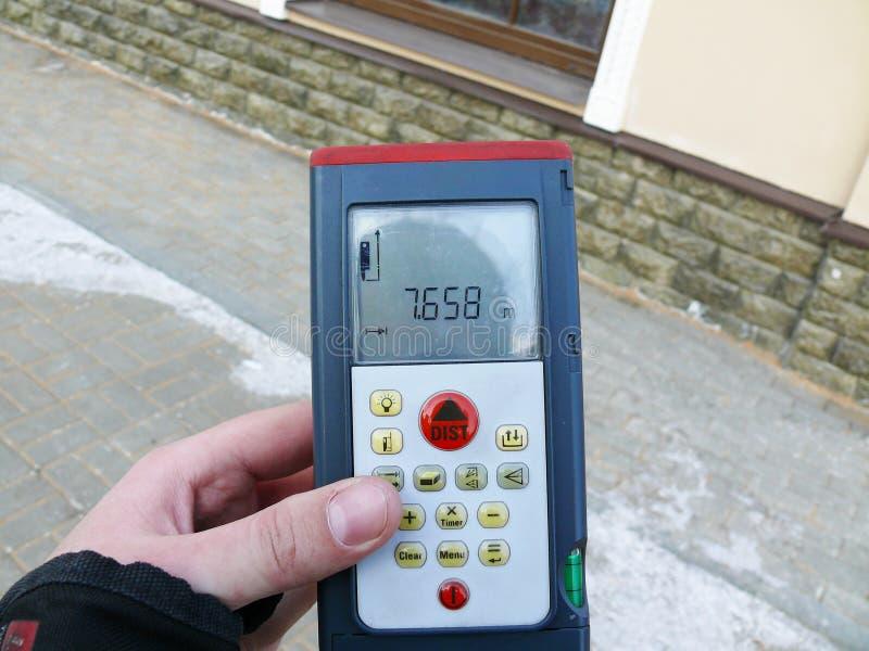 Удерживание измеряющий прибор для определять расстояние стоковое фото rf