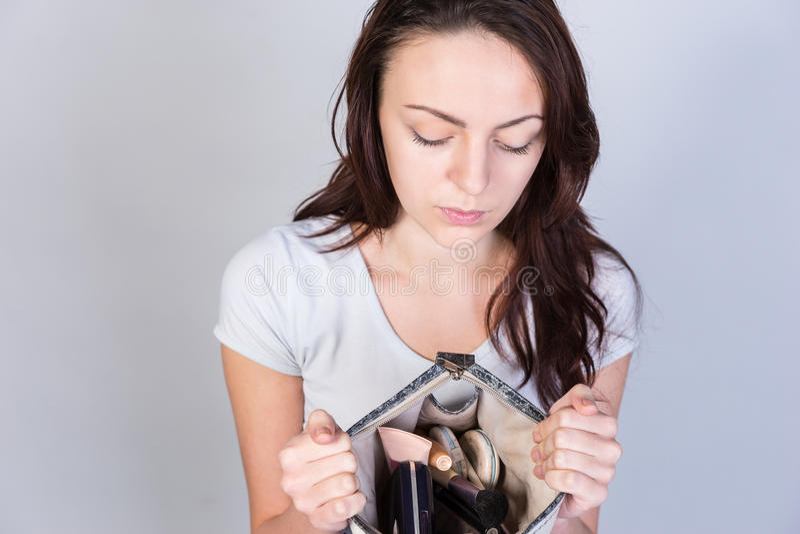 Удерживание молодой женщины раскрывает ее портмоне косметик стоковые фотографии rf