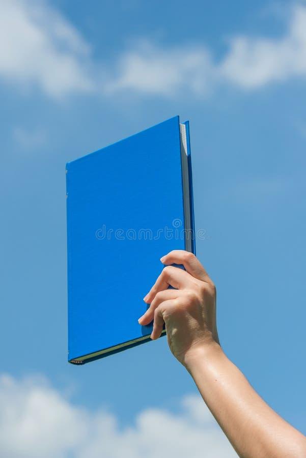 удерживание руки голубой книги над небом стоковая фотография