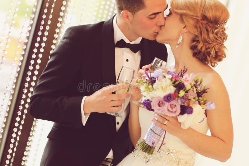 удерживание groom стекел шампанского невесты стоковые фото