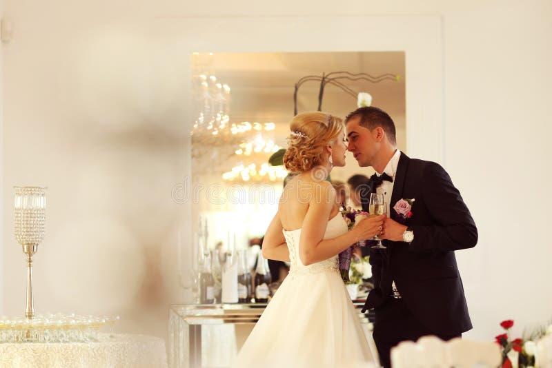 удерживание groom стекел шампанского невесты стоковая фотография