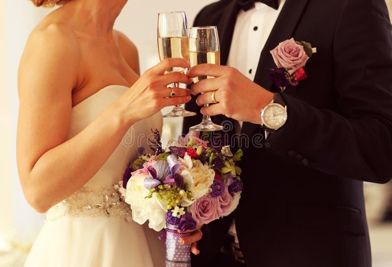 удерживание groom стекел шампанского невесты стоковые изображения