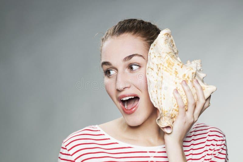 Удивительно девушка 20s удивленная звуком океана приходя от гигантской раковины стоковые изображения