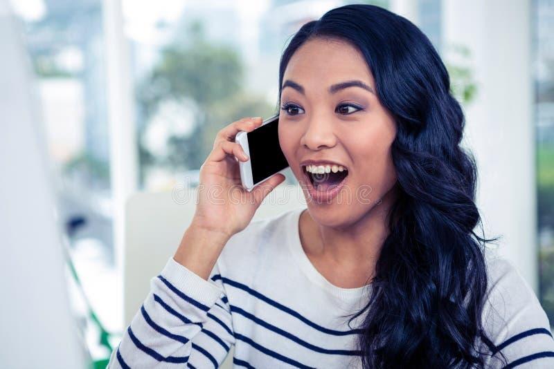 Удивленная азиатская женщина на телефонном звонке стоковые изображения