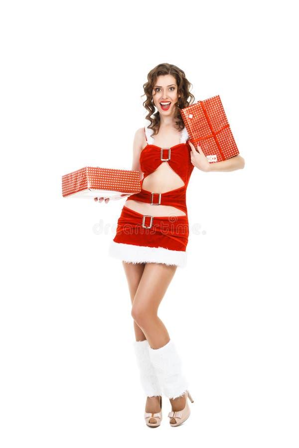 Удивленная девушка рождества изолированная на белой предпосылке держа подарок стоковые фото