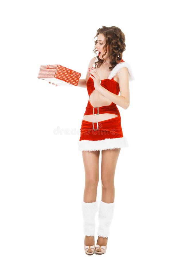 Удивленная девушка рождества изолированная на белой предпосылке держа подарок стоковые фотографии rf