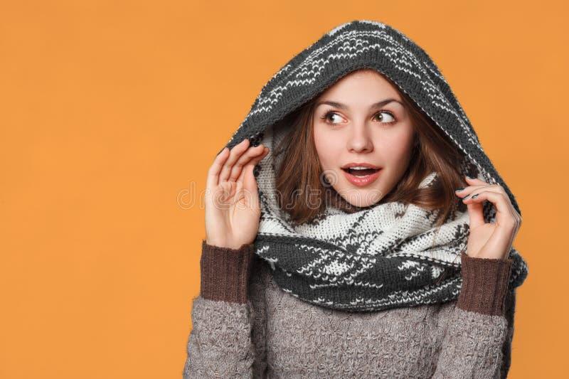 Удивленная девушка рождества нося связанный шарф носки Excited красивая усмехаясь девушка, концепция зимы, изолированная над оран стоковое фото