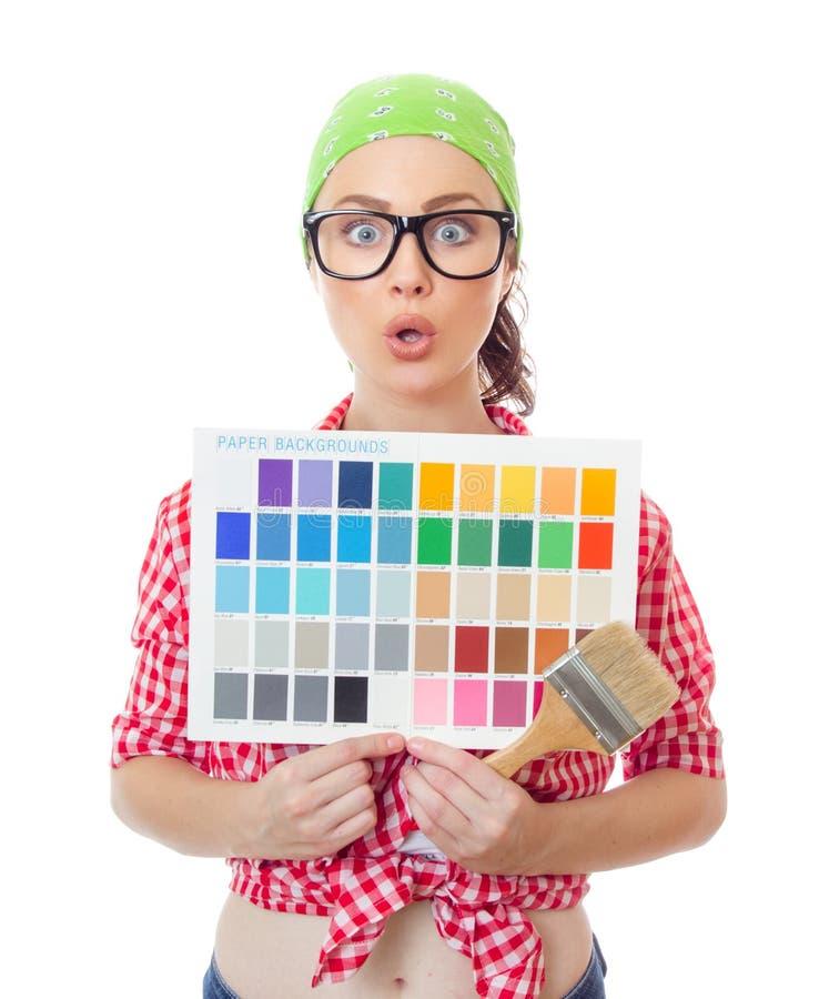 Удивленная женщина держа образцы paintbrush и цвета стоковые изображения
