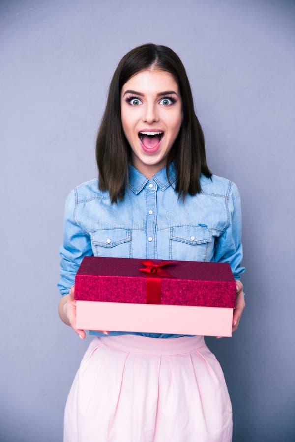 Удивленная женщина держа подарок и смотря на камере стоковые фотографии rf