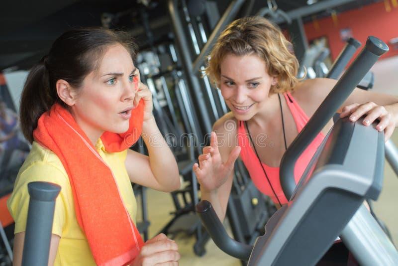 Удивленная женщина разговаривая с личным тренером пока работающ стоковые фото