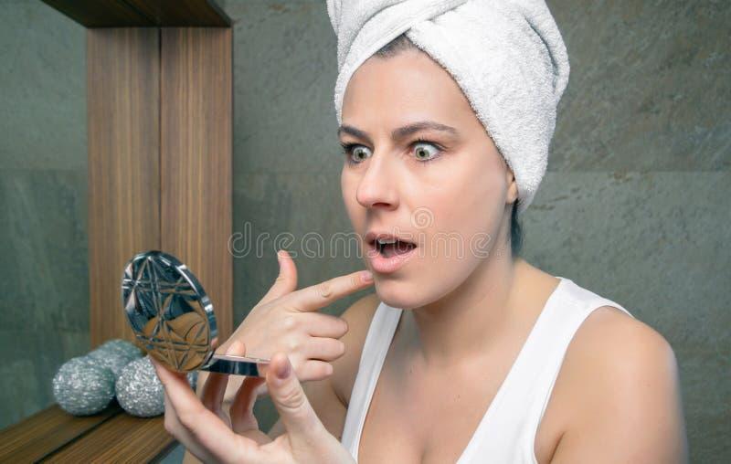 Удивленная женщина смотря цыпк угорь в зеркале стоковые фото