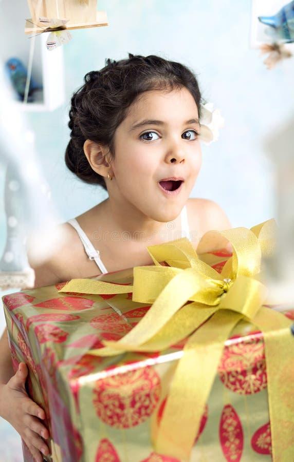 Удивленная маленькая девочка с подарками на день рождения стоковое изображение