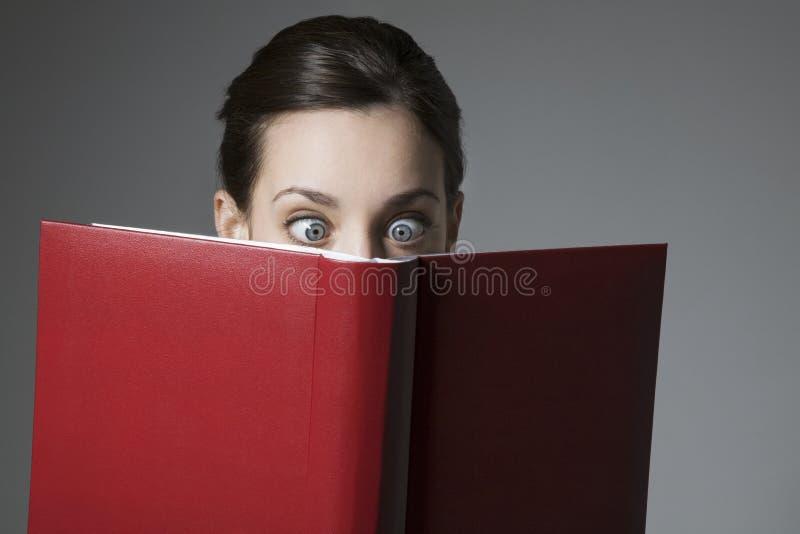 Удивленная молодая женская книга чтения с глазами широкими раскрывает стоковые фотографии rf
