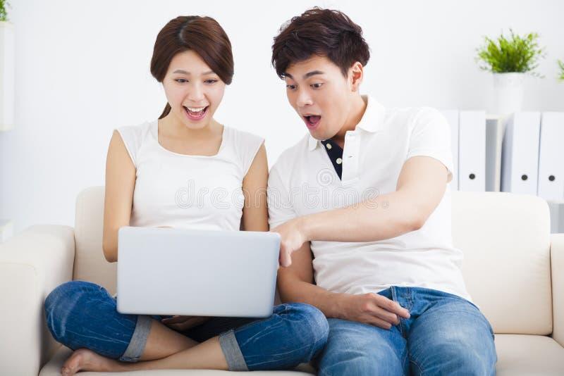 Удивленные пары на софе с компьтер-книжкой стоковые фото