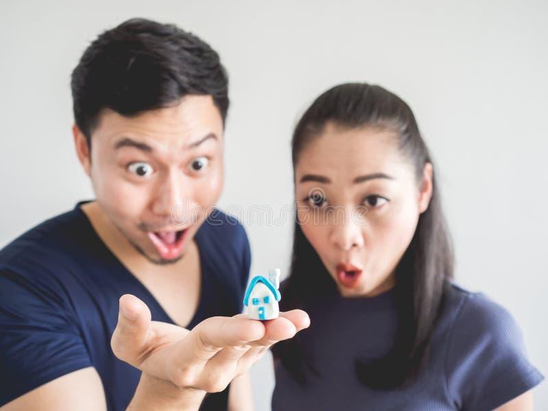 Удивленные пары с небольшим домом в руке стоковое изображение
