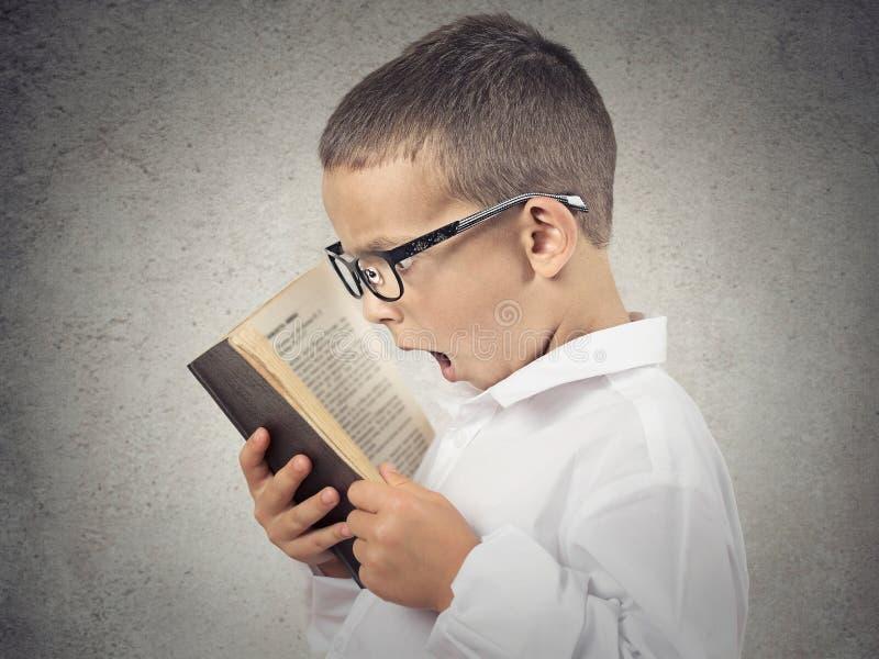 Удивленный мальчик, маленькая книга чтения человека стоковая фотография rf