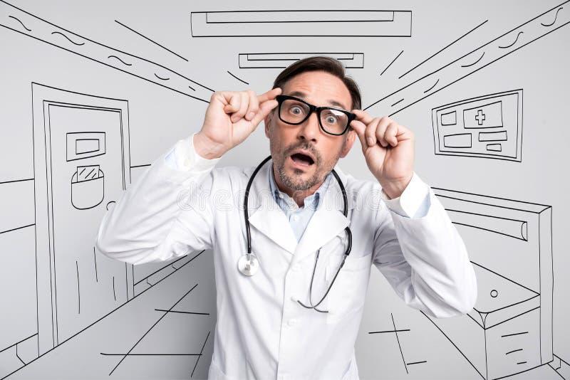 Удивленный доктор пугая через стекла стоковое фото rf