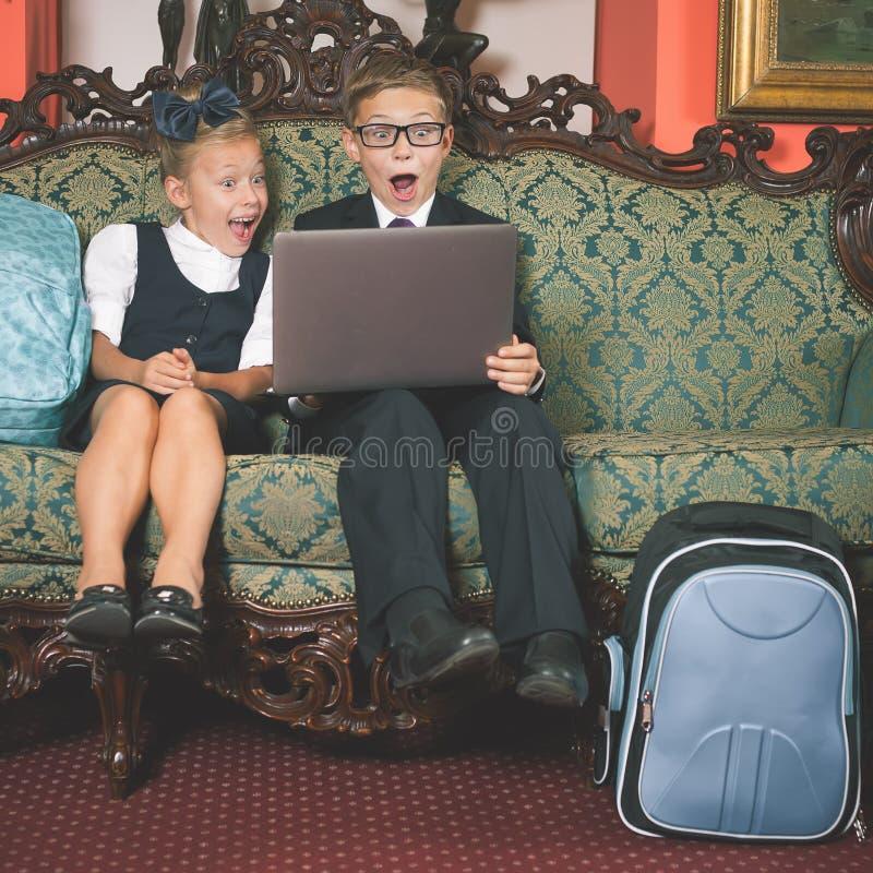 Удивленный портативный компьютер пользы детей школы стоковые фото