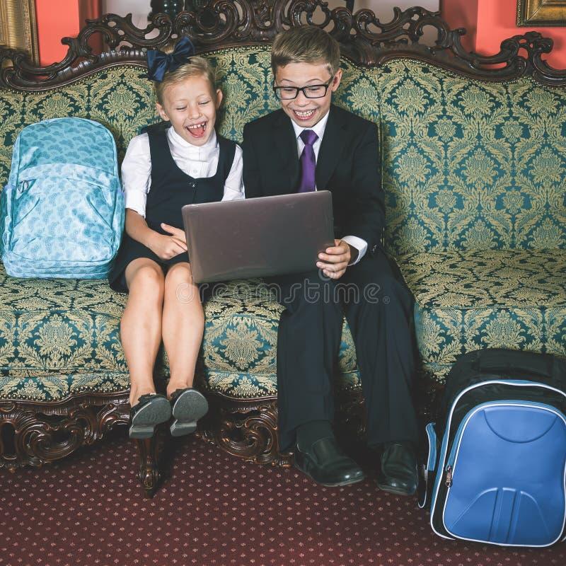 Удивленный портативный компьютер пользы детей школы стоковая фотография