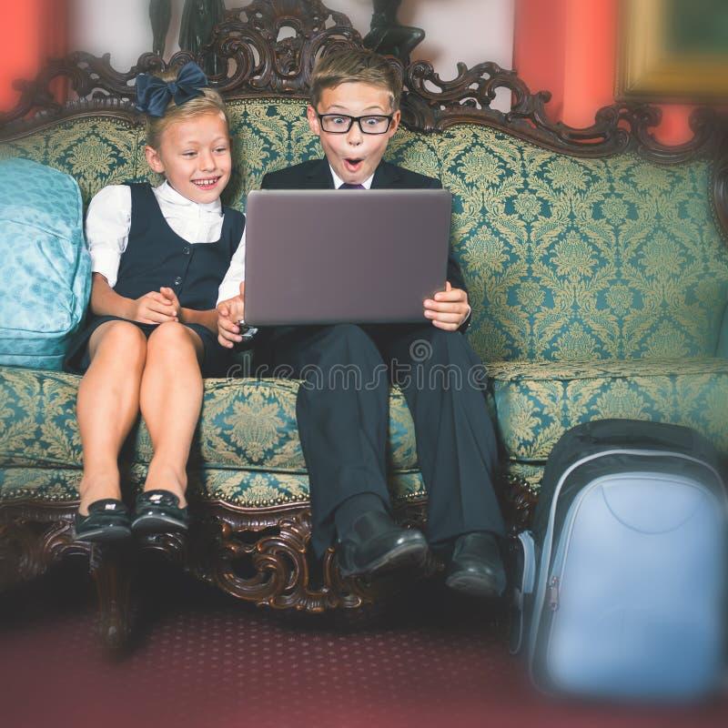 Удивленный портативный компьютер пользы детей школы стоковое изображение rf