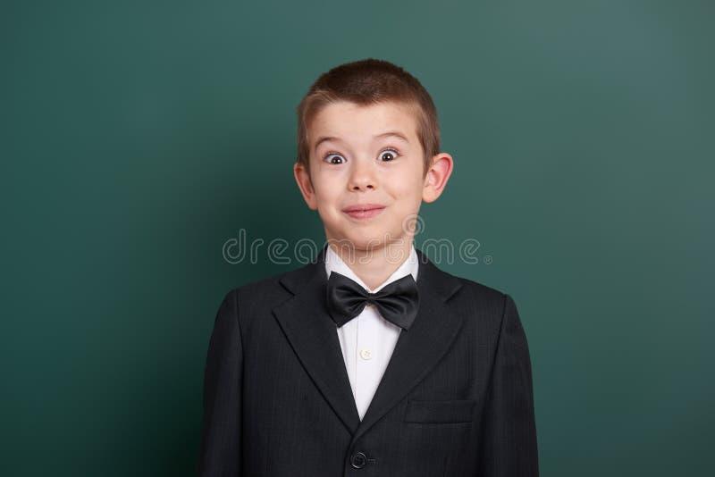 Удивленный портрет школьника около зеленой пустой предпосылки доски, одетой в классическом черном костюме, один зрачок, концепция стоковые изображения rf