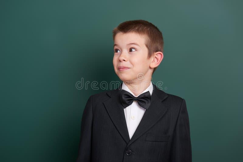 Удивленный портрет школьника около зеленой пустой предпосылки доски, одетой в классическом черном костюме, один зрачок, концепция стоковая фотография rf