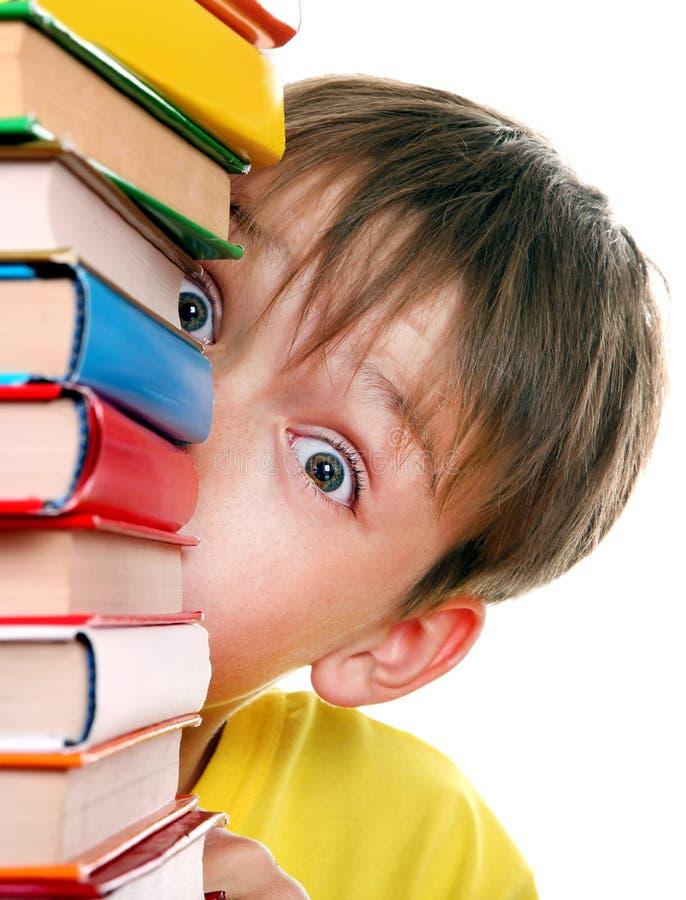 Удивленный ребенк за книгами стоковая фотография