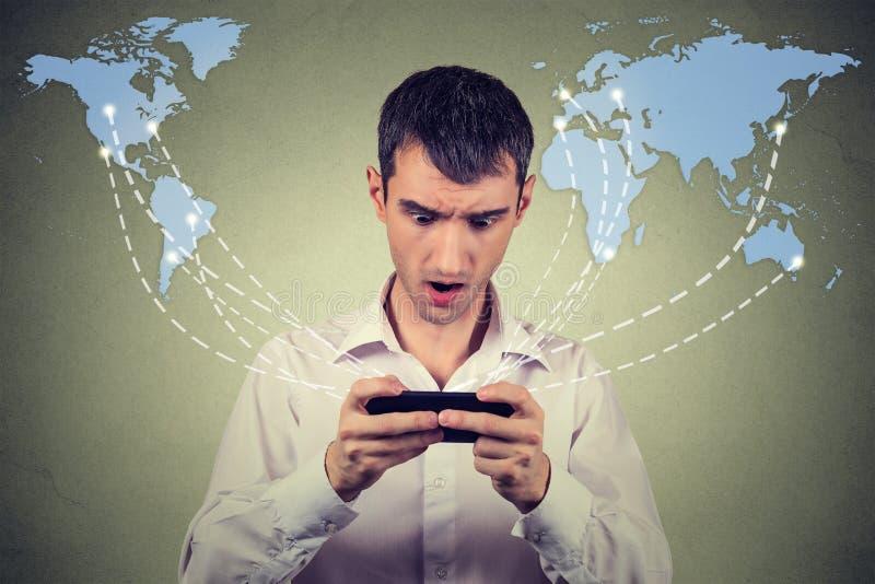 Удивленный человек держа соединенный smartphone интернет просматривать стоковое фото rf