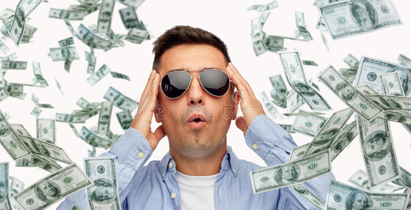 Удивленный человек под дождем денег доллара стоковые изображения rf